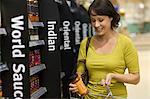 Woman choosing jar of sauce in supermarket Stock Photo - Premium Royalty-Free, Artist: Daryl Benson, Code: 6114-06600649