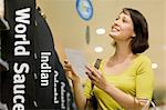 Woman in supermarket with shopping list Stock Photo - Premium Royalty-Free, Artist: ableimages, Code: 6114-06600652