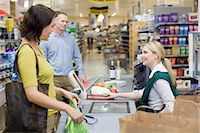 Cashier and customers at supermarket checkout Stock Photo - Premium Royalty-Freenull, Code: 6114-06600655