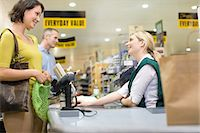 Cashier and customers at supermarket checkout Stock Photo - Premium Royalty-Freenull, Code: 6114-06600656