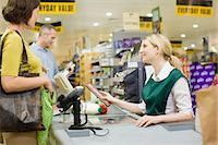 Cashier and customers at supermarket checkout Stock Photo - Premium Royalty-Freenull, Code: 6114-06600657