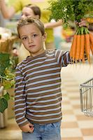 Boy in supermarket with bunch of carrots Stock Photo - Premium Royalty-Freenull, Code: 6114-06600683
