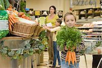 Boy in supermarket with bunch of carrots Stock Photo - Premium Royalty-Freenull, Code: 6114-06600685