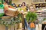 Boy in supermarket with bunch of carrots Stock Photo - Premium Royalty-Free, Artist: Blend Images, Code: 6114-06600685