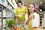 Mother and daughter getting milk in supermarket Stock Photo - Premium Royalty-Free, Artist: Blend Images, Code: 6114-06600694