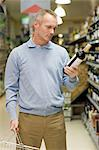 Man choosing wine in supermarket Stock Photo - Premium Royalty-Free, Artist: Ikonica, Code: 6114-06600709