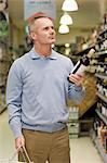A man holding a bottle of wine in a supermarket Stock Photo - Premium Royalty-Free, Artist: Susan Findlay, Code: 6114-06600710