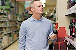 Man choosing wine in supermarket Stock Photo - Premium Royalty-Free, Artist: Jean-Christophe Riou, Code: 6114-06600713