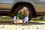 Boy sitting on ground with a cowboy hat, looking up at car Stock Photo - Premium Royalty-Free, Artist: Blend Images, Code: 6114-06600751