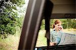 Woman using cellphone and map, viewed through a car Stock Photo - Premium Royalty-Free, Artist: Blend Images, Code: 6114-06600762