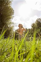 Boy in field with camera Stock Photo - Premium Royalty-Freenull, Code: 6114-06600779