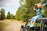 Boy with binoculars, sitting on roof of car Stock Photo - Premium Royalty-Free, Artist: CulturaRM, Code: 6114-06600784