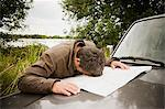 Frustrated man with head on map on car hood Stock Photo - Premium Royalty-Free, Artist: Ty Milford, Code: 6114-06600790