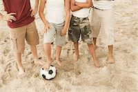 Boys standing on beach with football Stoc