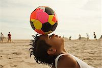 Boy balancing football on head Stock Photo - Premium Royalty-Freenull, Code: 6114-06600811