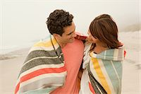 Couple wrapped up in colorful blanket on beach Stock Photo - Premium Royalty-Freenull, Code: 6114-06600915