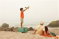 Family on beach, boy playing with toy plane Stock Photo - Premium Royalty-Freenull, Code: 6114-06600925