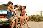 Three children sitting on back of estate car taking photographs Stock Photo - Premium Royalty-Free, Artist: CulturaRM, Code: 6114-06600938