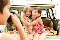 Three children sitting on back of estate car taking photographs Stock Photo - Premium Royalty-Freenull, Code: 6114-06600942