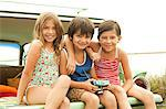Three children sitting on back of estate car wearing swimwear Stock Photo - Premium Royalty-Free, Artist: Blend Images, Code: 6114-06600944