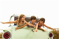 Three children in back of estate car with arms out Stock Photo - Premium Royalty-Freenull, Code: 6114-06600945