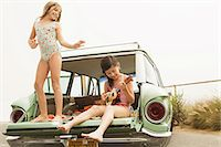 Girl dancing on car boot, another girl playing guitar Stock Photo - Premium Royalty-Freenull, Code: 6114-06600958