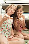 Two girls eating sandwiches on car boot Stock Photo - Premium Royalty-Free, Artist: Cultura RM, Code: 6114-06600962