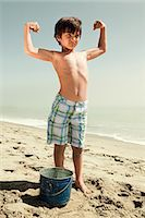 Boy standing on beach flexing muscles Stock Photo - Premium Royalty-Freenull, Code: 6114-06600969