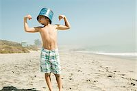 Boy with bucket on head, flexing muscles Stock Photo - Premium Royalty-Freenull, Code: 6114-06600970