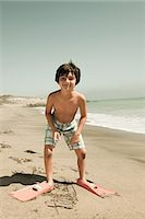 Boy standing on beach wearing swimming flippers Stock Photo - Premium Royalty-Freenull, Code: 6114-06600971
