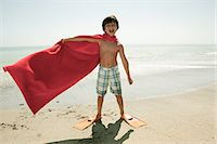 Boy wearing flippers and red cape on beach Stock Photo - Premium Royalty-Freenull, Code: 6114-06600973