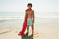 Boy wearing flippers and red cape on beach Stock Photo - Premium Royalty-Freenull, Code: 6114-06600975