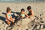 Children burying girl in sand Stock Photo - Premium Royalty-Free, Artist: Westend61, Code: 6114-06601010