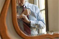 Man adjusting cuffs in mirror Stock Photo - Premium Royalty-Freenull, Code: 6114-06601049