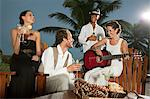 Bride and groom with friends, bride playing guitar Stock Photo - Premium Royalty-Free, Artist: Ikon Images, Code: 6114-06601092