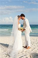 Bride and groom kissing on beach Stock Photo - Premium Royalty-Freenull, Code: 6114-06601095