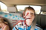 Boy blowing party blower in back seat of car Stock Photo - Premium Royalty-Free, Artist: Blend Images, Code: 6114-06601550