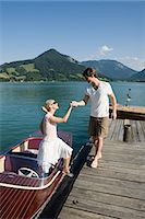 Man helping woman off a boat Stock Photo - Premium Royalty-Freenull, Code: 6114-06602158