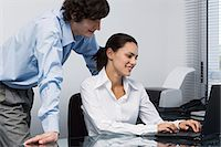 secretary desk - Man watching woman using laptop Stock Photo - Premium Royalty-Freenull, Code: 6114-06602348