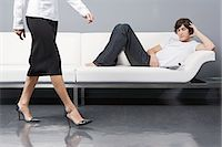 Man on sofa as woman walks by Stock Photo - Premium Royalty-Freenull, Code: 6114-06602365
