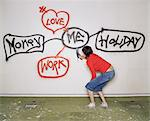 Woman spray painting graffiti on wall Stock Photo - Premium Royalty-Free, Artist: Blend Images, Code: 6114-06602384