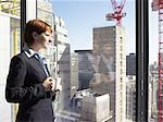 Businesswoman looking out of window Stock Photo - Premium Royalty-Free, Artist: Thomas Kokta, Code: 6114-06602563