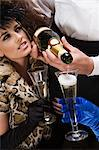 Waiter pouring two women champagne Stock Photo - Premium Royalty-Free, Artist: Blend Images, Code: 6114-06602881