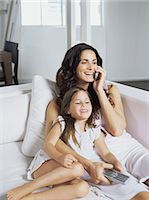 Mother and daughter sat on sofa Stock Photo - Premium Royalty-Freenull, Code: 6114-06603015