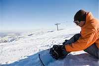 Man adjusting snowboard Stock Photo - Premium Royalty-Freenull, Code: 6114-06603328