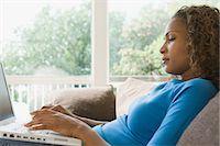 Woman on sofa using laptop Stock Photo - Premium Royalty-Freenull, Code: 6114-06603701