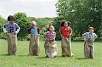 Kids having a sack race Stock Photo - Premium Royalty-Free, Artist: ableimages, Code: 6114-06603836