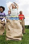 Girl winning sack race Stock Photo - Premium Royalty-Free, Artist: Blend Images, Code: 6114-06603850