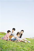 Asian family sitting in a field Stock Photo - Premium Royalty-Freenull, Code: 6114-06603945