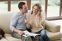person on phone with credit card - Couple looking at brochure on sofa Stock Photo - Premium Royalty-Freenull, Code: 6114-06603962